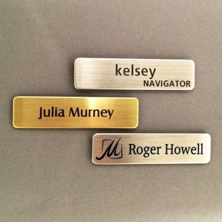 brass and silver name tags